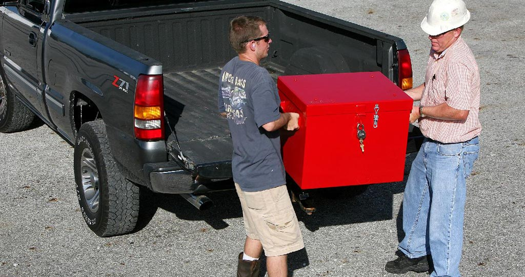 Two men unloading a day box off of a truck.
