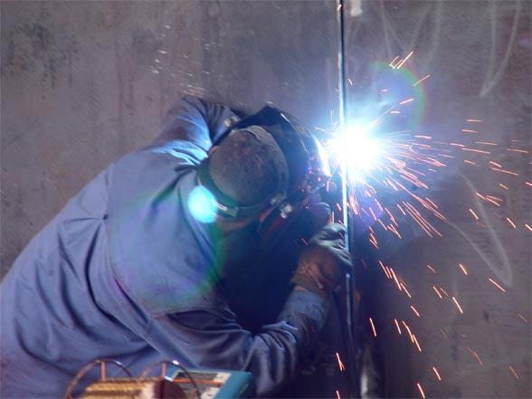 Welder working on a body panel